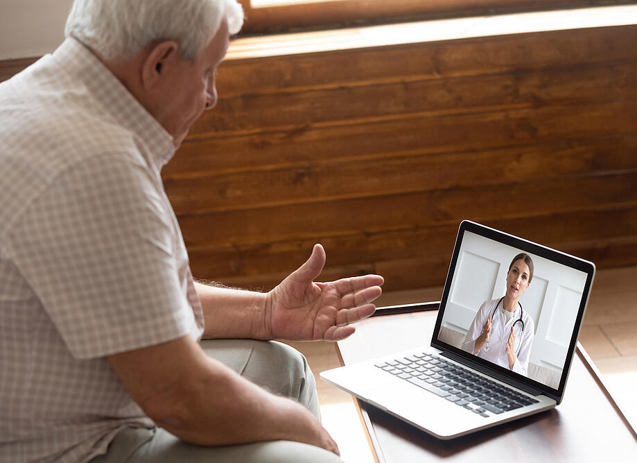 Man Talking to Doctor on Tablet
