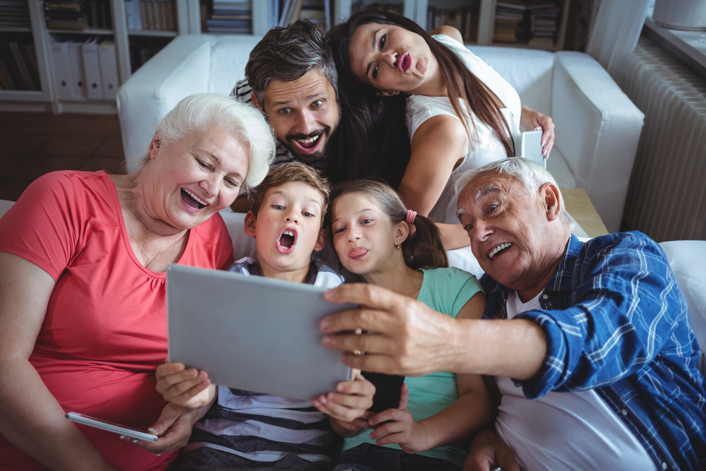 Multi-generation family taking a selfie on digital tablet in living room at home-1